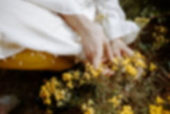 girl in white dress and yellow tights holding yellow flowers
