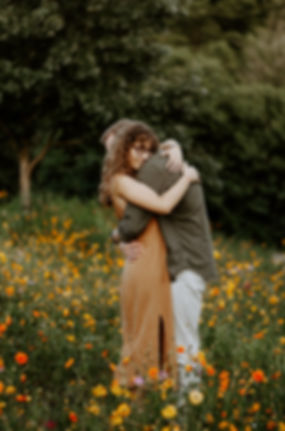 girl and boy hugging after engagement in a wildflower field