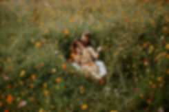engaged couple cuddling in a wildflower field at furman university
