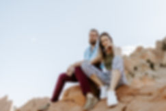 couple sits on red rocks and looks at camera