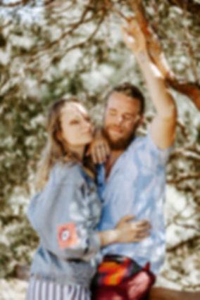 couple cuddling under a tree in colorado