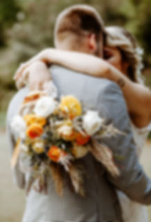 bridal bouquet laid over grooms back with checkered blazer