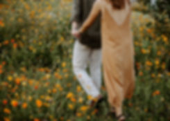 couple holding hands in a flower field at furman university
