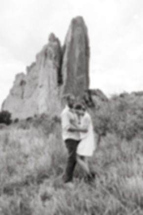 couple laughing in front of rock formation in black and white