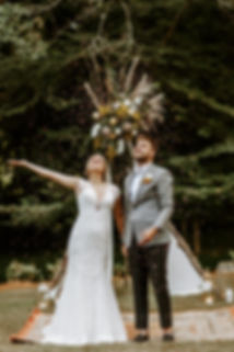 bride and groom toss flower confetti in air in front of teepee