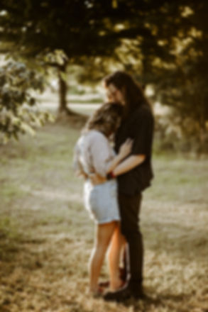 guy with long hair kissing the top of girls head