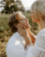 bride holding laughing grooms face