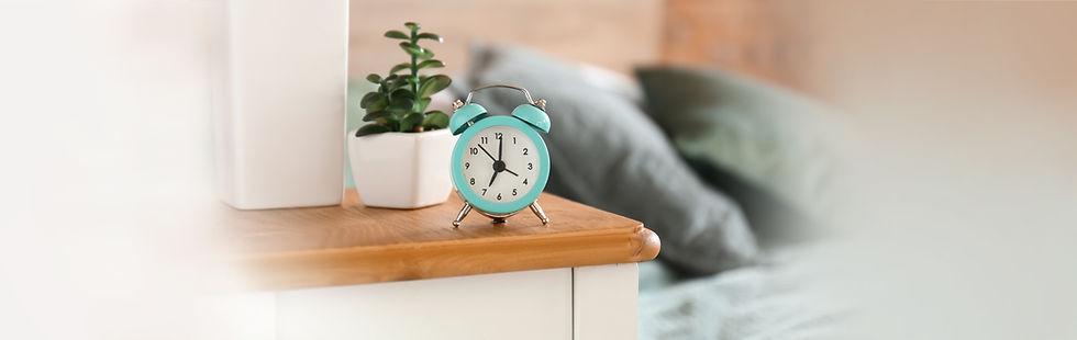 Wecker in türkis vor Bett