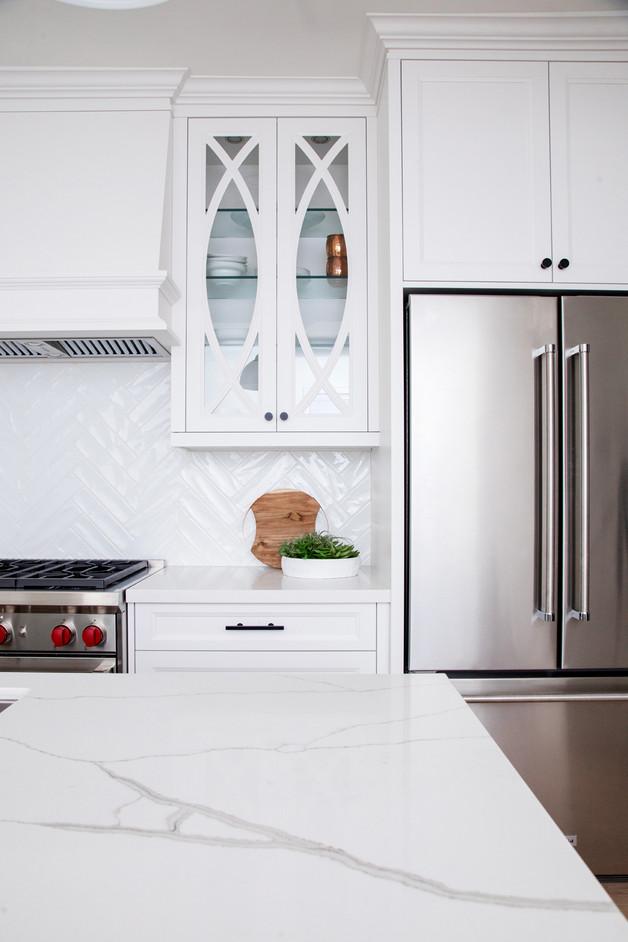 Glass kitchen cabinets, quartz counters with grey venining white kitchen white backsplash