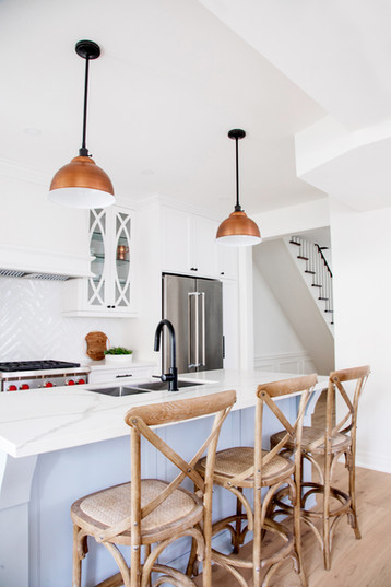 Transitional white kitchen with blue island and wooden bar stools. Copper pendants AC Interiors Design & Build Toronto Designers
