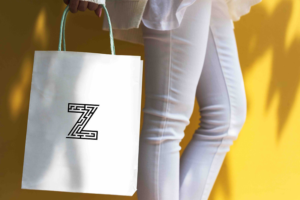 Gen Z wearing white jean against a bright yellow wall holding a white shopping bag