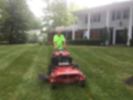 """Lawn care company in Saint Louis laying fresh stripes on lawn with a 48"""" Ferris mower"""
