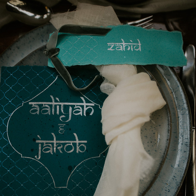 teal stationary with white linen napkin and speckeled blue plates