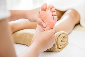 Professional therapist giving relaxing traditional thai reflexology foot massage to a woma