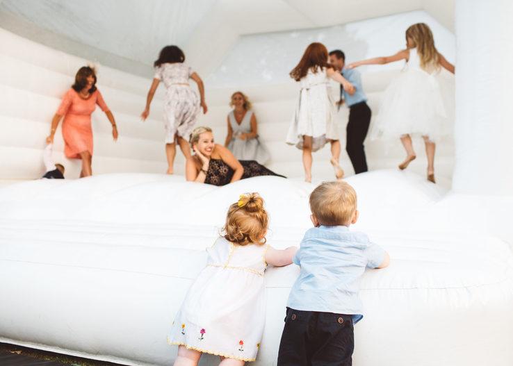 children jumping on white wedding bouncy castle.