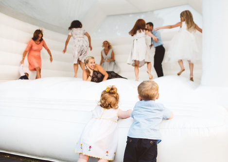 children jumping on white wedding bouncy castle.