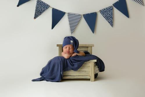 newborn boy in tiny bed