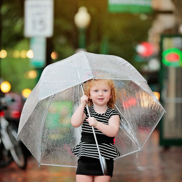 girl standing with umbrella in city