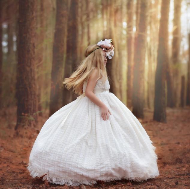girl twirling in dress in woods