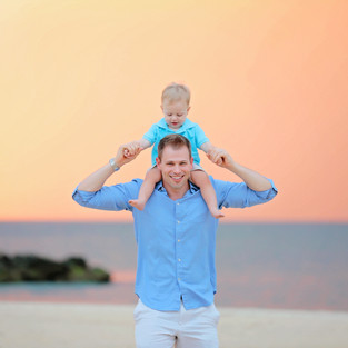 dad with boy on his shoulders at beach