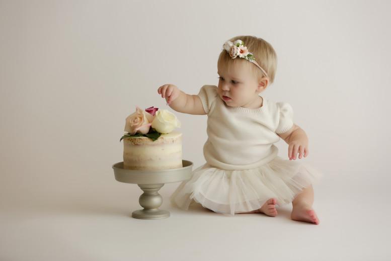 baby eating cake at cake smash