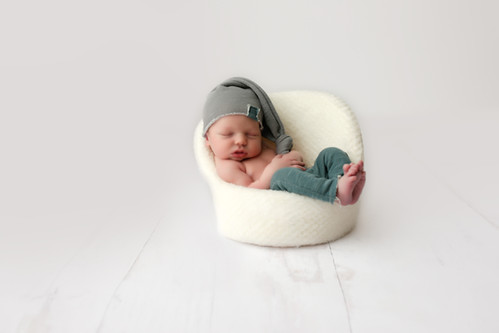 newborn boy sitting in newborn chair