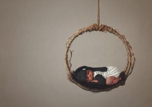 newborn boy hanging from swing