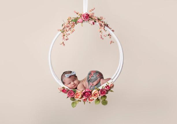 Newborn girl hanging from swing