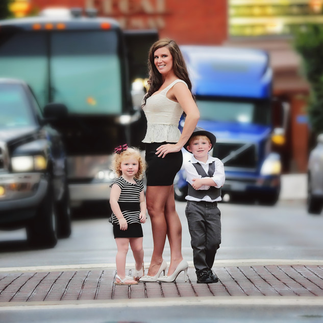 mom standing in city street with kids
