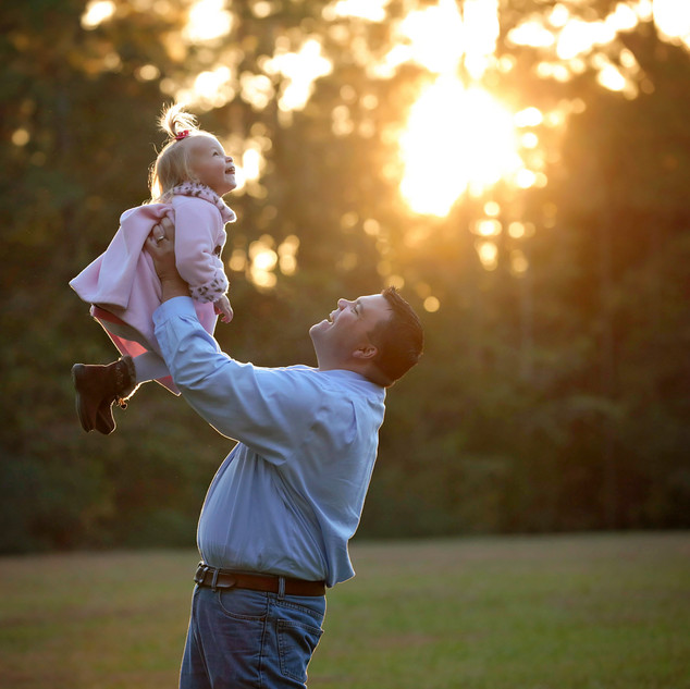 dad holding baby up with sunset