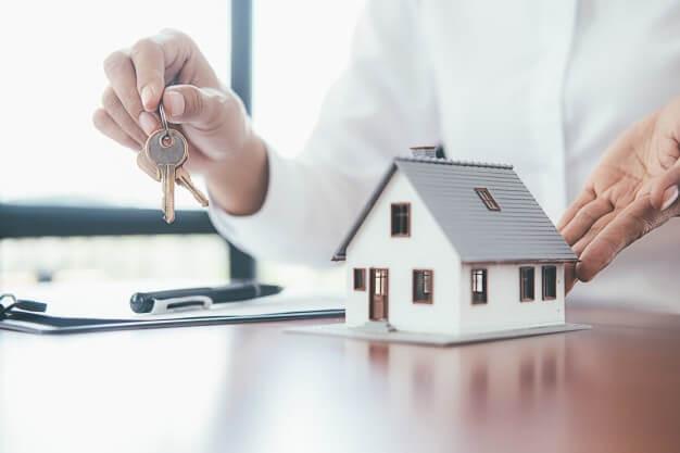 homem segurando em suas mão um molho de chaves e uma pequena maquete de uma casa