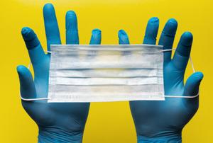 a imagem apresenta um fundo amarelo e duas mãos protegidas por luvas azuis que seguram uma máscara descartável
