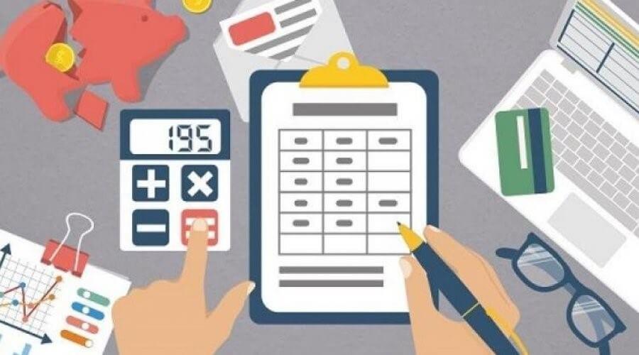 mãos manuseando  calculadora e uma prancheta , com um notebook e objetos pessoais ao lado direito