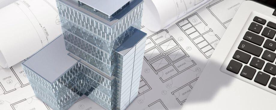 pequena maquete 3d de um edifício ao lado de um notebook e em cima de  desenhos