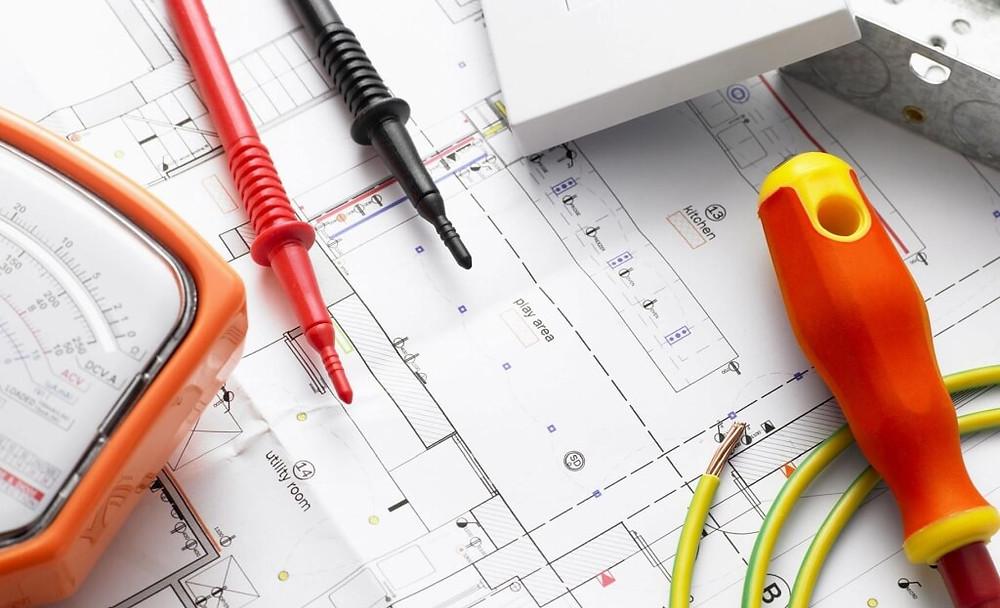 projeto elétrico ao fundo com ferramentas em primeiro plano