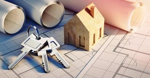 vários rolos de projeto ao fundo  e um molho de chaves e uma maquete de casa à frente