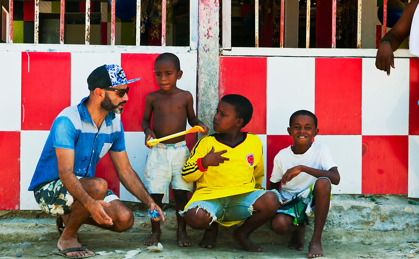 Blue Apple's in-house artist, Andres Molina, with children from Bocachica Village