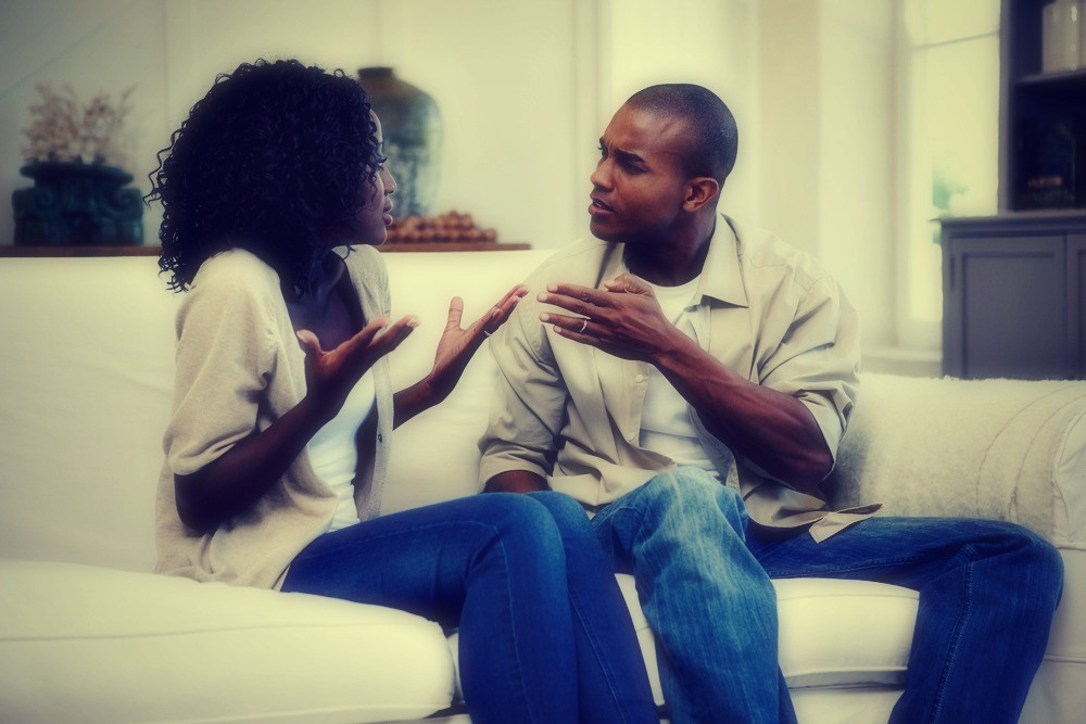 African couple arguing on sofa