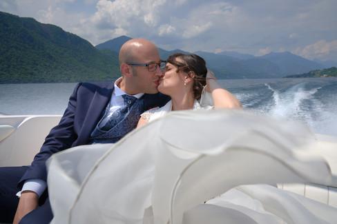 Sposi che si baciano in barca con abito svolazzante, fotografo matrimonio Novara,
