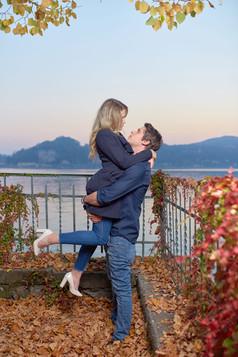 Fidanzati in braccio vicino al lago su foglie autunnali, servizio di fidanzamento, fotografo di matrimonio