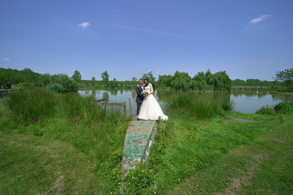 sposi in piedi su barca, laghetto cascina Riazzolo, fotografo matrimonio Novara,