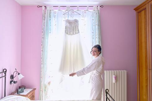 sposa vicino al vestito appeso sorride, fotografo matrimonio Novara