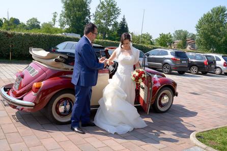 sposa che scende dalla macchina aiutata dal padre, fotografo matrimonio Novara,