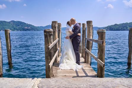 Sposi che si baciano sul pontile dell'isola di san giulio a Orta, figura intera, fotografo matrimonio Novara,