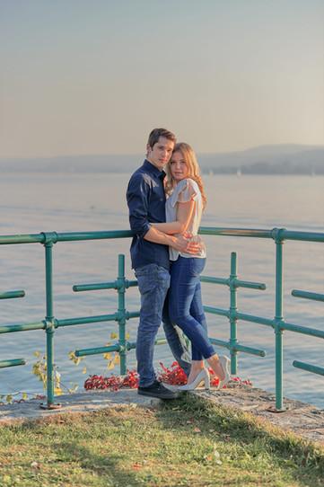 Fidanzati abbracciati vicino alla ringhiera e sfondo del lago, servizio di fidanzamento, fotografo di matrimonio