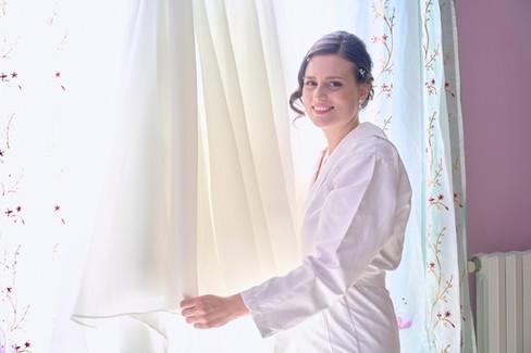 sposa  in piedi vicino all'abito bianco sorride, fotografo matrimonio Novara