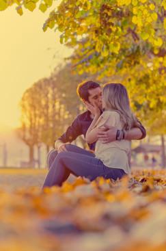 Bacio fidanzati seduti sulle foglie al tramonto con luce dorata, servizio di fidanzamento, fotografo di matrimonio