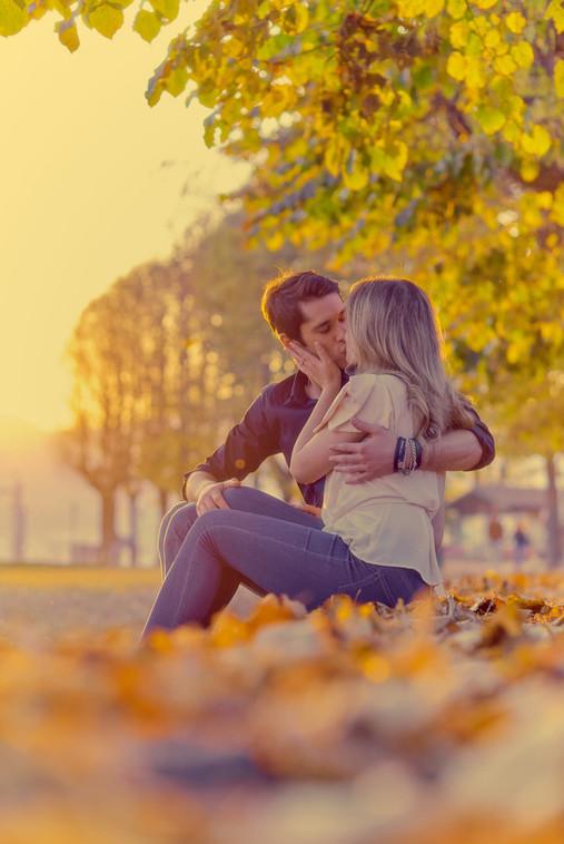 Bacio fidanzati seduti sulle foglie al tramonto con luce dorata