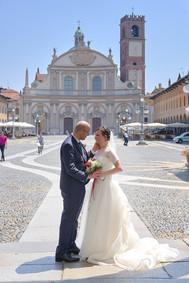 Sposi in piazza ducale a Vigevano, figura intera, fotografo matrimonio Novara