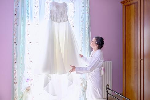 sposa che guarda l'abito appeso, preparativi sposa, fotografo matrimonio Novara